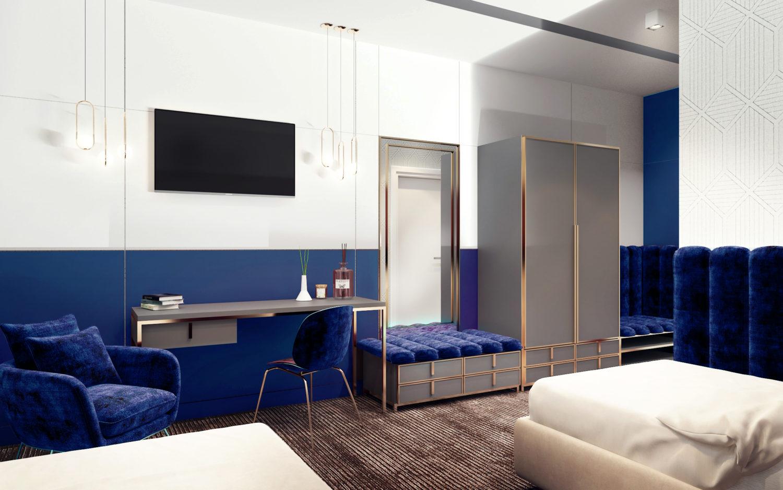 Pokój hotelowy dwuosobowy w kolorze szafirowym z telewizorem, wygodną wykładziną i ze złotymi elementami